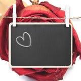 Räcka teckningshjärta på svart tavla med torr röd rosbakgrund, I Royaltyfri Bild