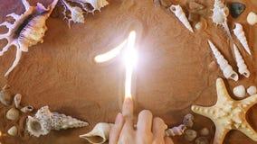 Räcka teckningsnumret ett 1 symbol i sanden pink scallop seashell Top beskådar arkivfilmer