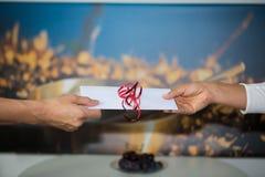 Räcka ut pengarkuvertet till personalen, drickspeng royaltyfria foton