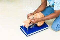Räcka utbildning med den head medicinska attrappen på CPR, i nöd- refresher till hjälp av läkaren royaltyfri fotografi