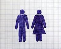 Räcka utdragna man- och kvinnadiagram på arket av rutigt papper Royaltyfri Bild