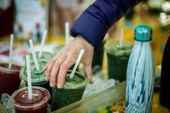 Räcka val upp av en kall grön smoothie på bondens marknad royaltyfria foton
