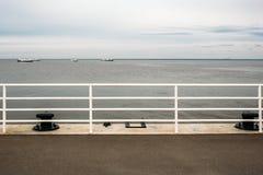 Räcke av pir med havsikt i molnig lugna dag med skepp på horisont arkivfoto