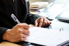 Räcker affärsmannen som undertecknade dokumentet. Royaltyfria Bilder