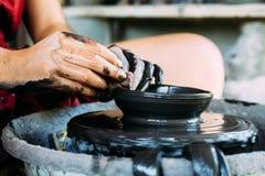 Räcker closeupen som arbetar på krukmakerihjulet med keramik Arkivfoton