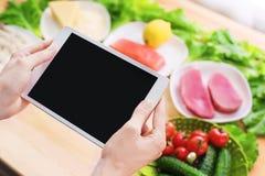 Räcker den bästa sikten för närbilden av kvinnlign att rymma en minnestavladator med en tom skärm som omges av sund mat på ett he Fotografering för Bildbyråer