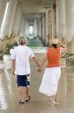 Räcker den mogna mannen för romantiker & kvinnainnehavet att gå på stranden royaltyfri foto