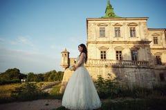 Räcker den unga bruden för den ursnygga brunetten och det charmiga brudguminnehavet a Royaltyfri Foto