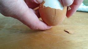 Räcker ett ägg på ett träbrädeprotein stock video