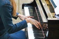 Räcker försiktigt att leka en melodi på pianot Royaltyfri Bild