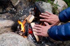Räcker på campfire Royaltyfri Foto