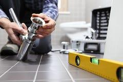 Räcker rörmokaren på arbete i ett badrum, rörmokerireparationsservice, som arkivbilder