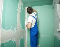 Räcker stuckatören på arbete Applikation av murbruken på väggen Royaltyfri Fotografi