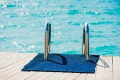 Räckestege som ner går till pir in i havet royaltyfri bild