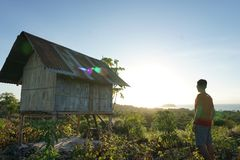 Räckvidden för den unga mannen till överkanten av kullen tycker om därefter soluppgången uppifrån arkivbild