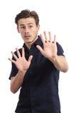 Rädd man i försvarinställning som gör en gest stoppet med händer Arkivbilder