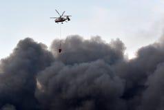 Rädda helikoptern med vatten och röka från branden royaltyfria foton