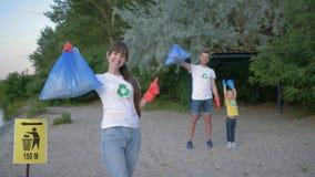 Räddningplanet, stående av den unga volontärkvinnan i gummihandskar med avskrädepåsen nära pekaretecken på bakgrundsman och arkivfilmer