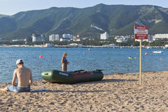 Räddningsaktionfartyg och ett tecken som säger att varna! Ingen simning! Fara av den dödliga skadan på en strand i Gelendzhik Arkivfoton
