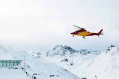 Räddningsaktionhelikopterlandning på lutningar på skidar semesterorten i alpina berg Nöd- olycksservice royaltyfria bilder