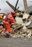 Räddningsarbetare och hund på byggnad Arkivfoto
