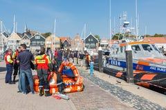 Räddningsarbetare som visar räddningsaktionutrustning i holländsk hamn av Urk Royaltyfria Bilder