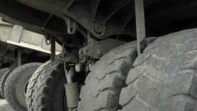 Räder und Fahrgestelle des enormen LKWs Lastwagen im Steinbruch für Stein und Kiesgewinnung stock footage