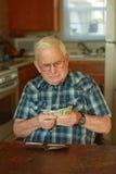 räkna manpengarpensionären Arkivbild