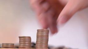 Räkna och sätt pengarmynt till bunten av mynt stock video