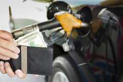 räkna pengar med bensin som tankar bilen arkivbild