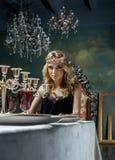 Räknar samman den bärande kronan för den unga blonda kvinnan i felik lyxig inre med tomma antika ramar rikedom Royaltyfria Bilder