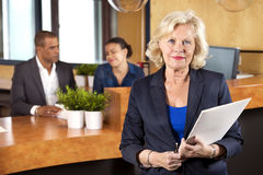 Räknare för affärskvinnaHolding File At mottagande Royaltyfria Bilder
