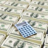 Räknemaskin överst av dollarräkningar Fotografering för Bildbyråer