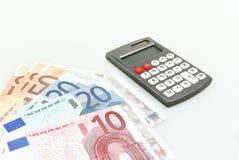 Räknemaskin-, euroanmärknings- och euromynt som isoleras på vit Arkivfoto