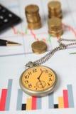 Räknemaskin, klocka och buntar av mynt Arkivbilder
