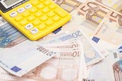 Räknemaskin med euroanmärkningar Arkivbilder