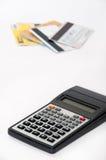 Räknemaskin med kreditkortar i bakgrunden Arkivbild