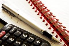 Räknemaskin med pennan på papper Arkivfoto