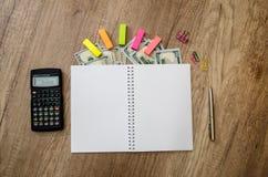Räknemaskin, notepad med pennan och oss dollar Arkivbilder