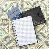 Räknemaskin och anteckningsbok på dollar Arkivbilder