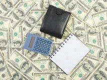 Räknemaskin och anteckningsbok på dollar Arkivbild