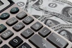 Räknemaskin och dollar på skrivbordet arkivfoto