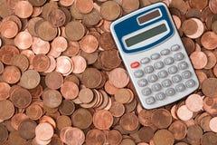Räknemaskin och hög av mynt för eurocent Arkivfoto