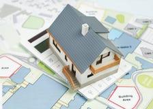 Räknemaskin och modell House på ritningar Royaltyfri Foto