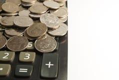 Räknemaskin och mynt på den vita bakgrunden royaltyfri foto