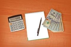 Räknemaskin och notepad som ligger på sedlar på det wood skrivbordet Royaltyfria Bilder