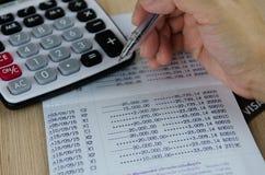 Räknemaskin och penna på bankkontobankbok royaltyfria bilder