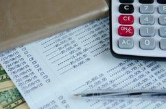 Räknemaskin och penna på bankkontobankbok med dollarsedeln royaltyfri bild