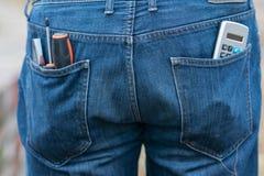 Räknemaskin och skruvmejslar i de tillbaka jeansfacken Royaltyfria Bilder