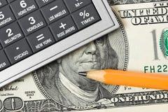 Räknemaskin, pengar och blyertspenna Arkivbild